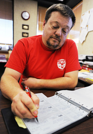 Kevin Kollmeyer, president of the Communication Workers of America Local 6313 in Joplin, signs checks in the office.<br /> Globe | T. Rob Brown