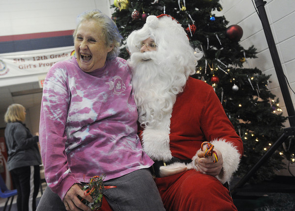 Globe/Roger Nomer<br /> Patricia Ortiz, Joplin, enjoys a visit with Santa at the Salvation Army Christmas lunch on Wednesday.