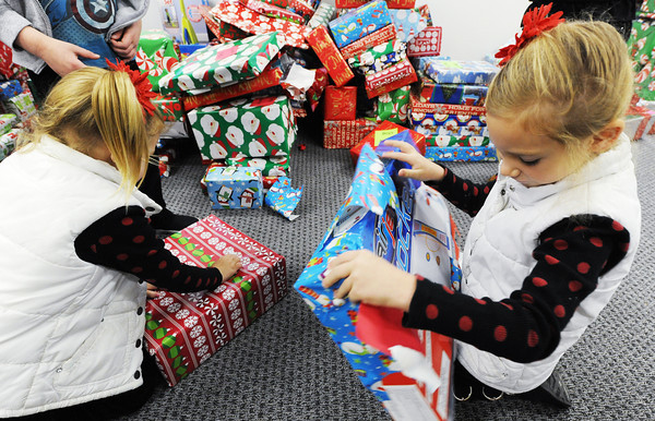 Sisters Kennady Schwab (left), 4, and Ella Schwab, 7, both of Joplin, open presents from Christpoint Church as part of the Ultimate Christmas Experience's second year Saturday afternoon, Dec. 14, 2013, at the Joplin church. Childrens Pastor Orlando Garcia said about 300 children and their parents attended the annual event. The church gave each of the children a present of a toy as well as giving out about 50 care baskets, 15 bicycles and 25 gift cards to Walmart.<br /> Globe | T. Rob Brown