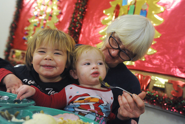 Globe/Roger Nomer<br /> Virginia Tosh, Webb City, feeds her grandchildren Bentley, 2, and Nevaeh, 1, Armstrong, Joplin, at the Christmas lunch at First Community Church on Wednesday.
