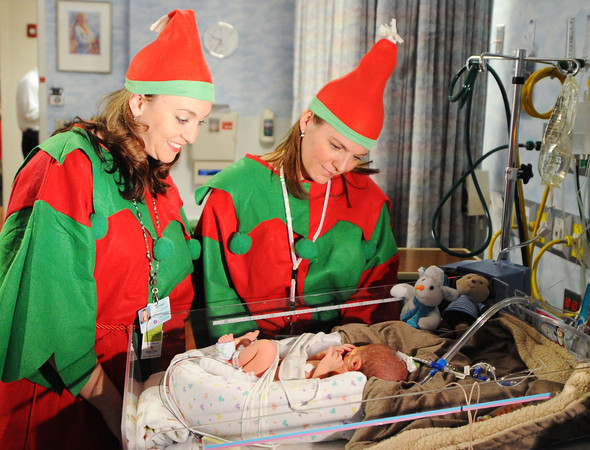 Elves Tiffany Stout (left), human resources coordinator, and Heather Lesmeister, director of Children's Miracle Network, visit Isaiah Wiehe, born Dec. 20 and currently in the NICU at Freeman West in Joplin on Monday morning, Dec. 23, 2013.<br /> Globe | T. Rob Brown