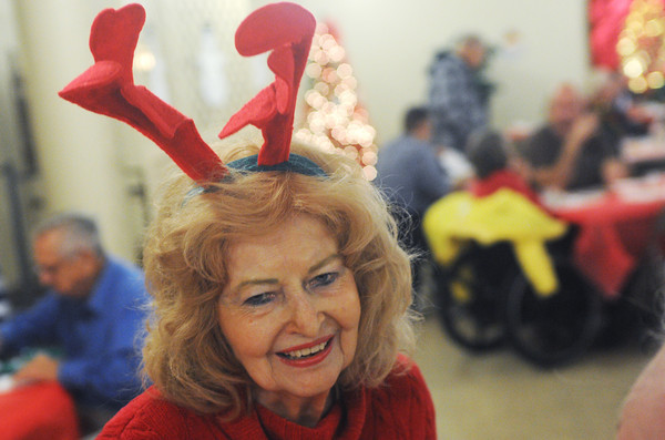 Globe/Roger Nomer<br /> Sporting festive headwear, Charlotte Barnett, Joplin, volunteers at the First Community Church Christmas lunch on Wednesday.