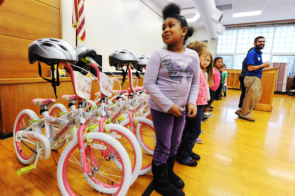 Second grader Zephania Carlos smiles for one of her teachers as she gets her picture taken next to a row of bicycles Thursday afternoon, Dec. 19, 2013, at Eastmorland Elementary School. Academy Sports donated a total of 30 bicycles and accompanying safety helmets to the school, with 15 pink bicycles for girls and 15 black bicycles for boys.<br /> Globe | T. Rob Brown