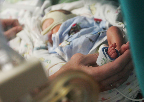 Globe/Roger Nomer<br /> Amber Turner holds her daughter Mary's foot during a visit to the Freeman NICU. Because the girls are in incubators, the Turners have limited physical contact with them.