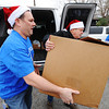 Con-Way Truckload employees Tim Franklin (left), precurement coordinator, and Kevin Coss, facilities maintenance, deliver a load of food items Friday afternoon, Dec. 20, 2013, for the St. Peters Outreach, 807 S. Moffett, in Joplin.<br /> Globe | T. Rob Brown