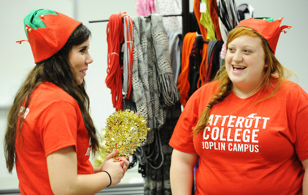 "Carolers Shalae Brown (left), 17, and Cloie Frencken, 18, both with the East Newton High School Patriot Singers, perform ""Rudolph the Red-nosed Reindeer"" during the Vatterott College Christmas party Thursday afternoon, Dec. 19, 2013, at the Joplin campus.<br /> Globe 