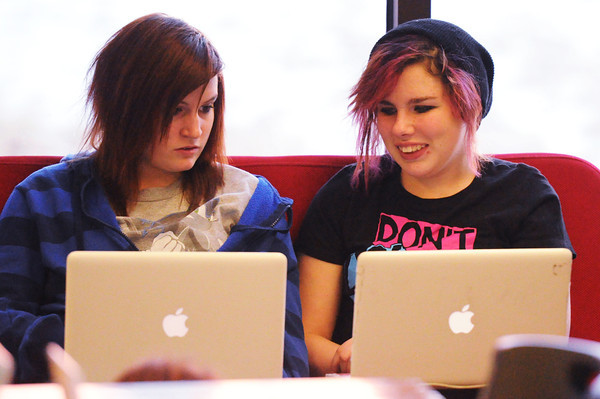 """Joplin High School students and Joplin Public Library patrons Sarah Adams (left), 14, and friend Clarissa Collins, 15, work on their school laptops in the teen library Thursday afternoon, Dec. 12, 2013. """"Our shelves are full. Whenever I buy a book, I'm so out of space that I have to get rid of a book,"""" said Cari Rerat, teen librarian.<br /> Globe 