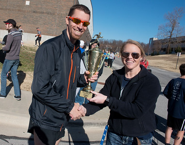 Globe/Roger Nomer Austin Bunn, Nevada, accepts the trophy for first overall male finisher from Sally Pennington, race director, following Saturday's Chilly 5K at the south Joplin YMCA.