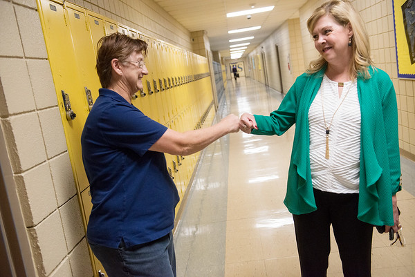 Globe/Roger Nomer<br /> Harrison Superintendent Melinda Moss gives a fist bump to teacher Diana Hodges during a conversation about academic improvements at the high school on Friday.