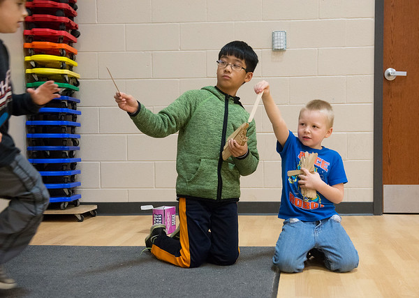 Globe/Roger Nomer<br /> Duc Dang, fourth grade, left, and Dalton Riggle, first, help hand out popsicle sticks to runners on Monday, Dec. 5, at Columbia Elementary.