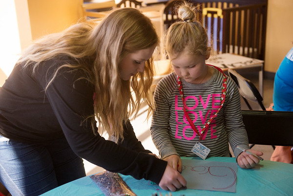 Globe/Roger Nomer<br /> Alyvia Warstler helps Grace Coate, 6, with her name tag decoration on Tuesday at the Victory Ministry and Sports Camp's winter camp.