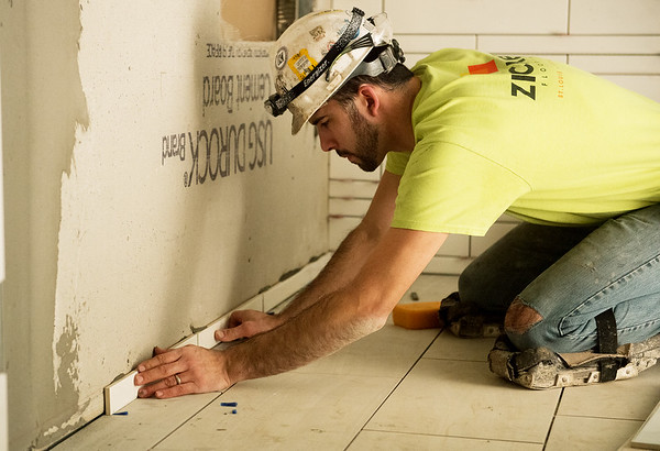 Globe/Roger Nomer<br /> Peter Roman, with Zickel Flooring, works with tile on Thursday at the new Joplin Public Library.