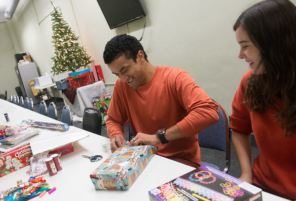 Globe/Roger Nomer<br /> Andrew and Amy Fink, house managers at Souls Harbor, wrap presents on Tuesday at the shelter.