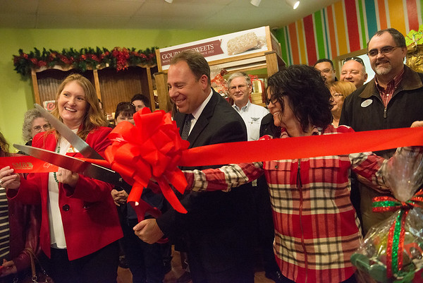 Globe/Roger Nomer<br /> (from left) Jennifer Reeves, Wayne and Cara Adolphsen cut the ribbon on Monday during the reopening of the Candy House.