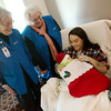 Globe/Roger Nomer<br /> Helen Moss, left, and Lorinda Southard visit with Natasha Lane and her son Ryder England on Thursday at Mercy Hospital. Volunteers wit the Mercy Auxiliary have made stockings and stocking caps to be given to every baby born in the month of December at the hospital.