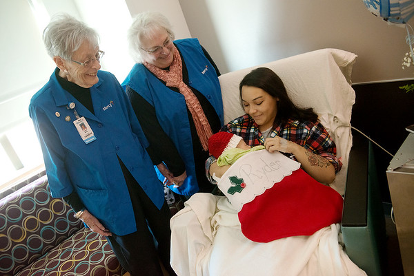 Globe/Roger Nomer Helen Moss, left, and Lorinda Southard visit with Natasha Lane and her son Ryder England on Thursday at Mercy Hospital. Volunteers wit the Mercy Auxiliary have made stockings and stocking caps to be given to every baby born in the month of December at the hospital.