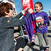 Globe/Roger Nomer<br /> Anne Windsor greets Kaliyah Cotten, 4, at the finish line with a medal on Saturday during the Frozen Fun Run at the downtown Joplin YMCA.