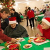 Globe/Roger Nomer<br /> Tom Hamsher serves dessert to David and Mary Putnam on Monday at First Community Church's Christmas meal in Joplin.