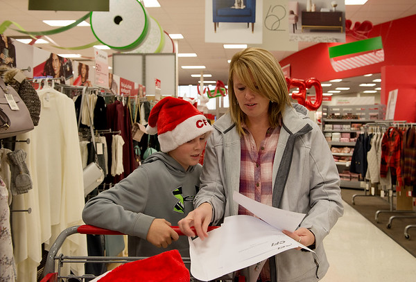 Globe/Roger Nomer<br /> Brandon, 10, and Lisa Stice shop for a family on Thursday at Target during the CFI Truckloads of Treasure event.