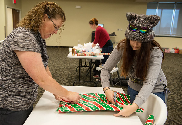 Globe/Roger Nomer<br /> Angela Bennett, administrative assistant for criminal justice and social work, left, and Hanna Shyers, a Missouri Southern senior from Miami, wrap a present on Monday at Billingsly Student Center.