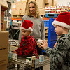 Globe/Roger Nomer<br /> Parker, 8, right, and Hunter, 5, volunteer with their mother Julie Brashears, Webb City, on Monday at Crosslines.