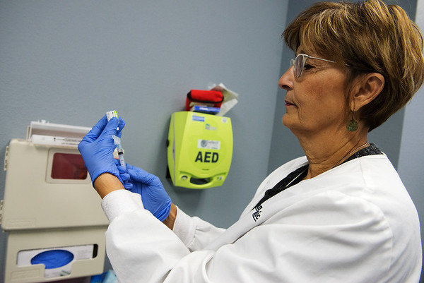 Globe/Roger Nomer<br /> Mary Fetters, a registered nurse at the Joplin Community Clinic, demonstrates a flu vaccine on Wednesday.