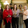 Globe/Roger Nomer<br /> Lori Haun, executive director of the Joplin Downtown Alliance, left, awards winners in the downtown Christmas window decorating contest including Linda Teeter, Urban Art Gallery, for most creative, Floyd and Jacqueline Hackett and Madison Riddle, Hackett Hot Wings, for most festive, and Rachel Goodrich, center, Net Vendor, for people's choice, on Thursday at Joplin City Hall.