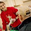Globe/Roger Nomer<br /> Kelly O'Toole talks with visitors as she busses tables on Monday at First Community Church's Christmas meal in Joplin.