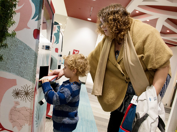 Globe/Roger Nomer<br /> Peter Cornett, 2, helps his mother Sheri, Joplin, check out books on Wednesday at the Joplin Public Library.