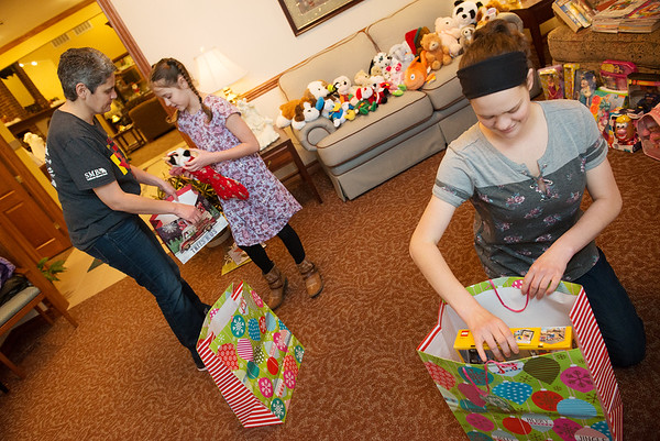 (from left) Jodi, Hannah and Amber Helwig prepare gifts at the Ronald McDonald House in Joplin on Thursday, Dec. 13.<br /> Globe   Roger Nomer