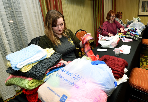 From the left: Raquel Reno and Leah Shipley, of Missouri Southern's League of Lions and veteran volunteer Page Urrows help tag new scarves, hats and gloves for distribution throughout the Joplin community as part of the Chase the Chill program on Thursday night at Homewood Suites. Urrows has volunteered each year since the program began four years ago.<br /> Globe | Laurie Sisk