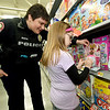 Joplin Police Officer Lacey Baxter assists Presley-Lynn Belt, 8, as she looks at the selection of popular LOL products during the Shop with a Cop event on Saturday at Walmart on 15th and Range Line.<br /> Globe | Laurie Sisk