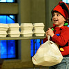 Three-year-old volunteer Asher Cullers helps pack meals for delivery during First Christian Church's community Christmas dinner on Tuesday at the church.<br /> Globe | Laurie SIsk