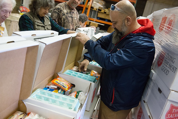 Russ Hibbard, associate pastor at Calvary Chapel, checks donation boxes at the Salvation Army warehouse on Tuesday.<br /> Globe | Roger Nomer
