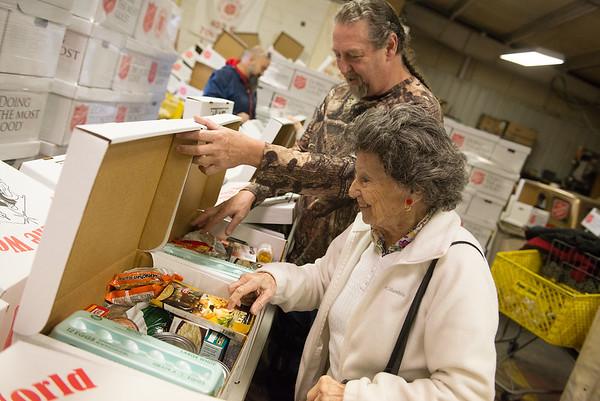Rob Barber and his mother Adele, visiting from Merritt Island, Fla., check donation boxes at the Salvation Army warehouse on Tuesday.<br /> Globe | Roger Nomer