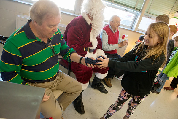 Kiwanis members Richard LaNear, left, and Loren Smith help Santa distribute gifts to Jefferson Elementary students, including Ava Edwards, fourth grade, on Tuesday during the Kiwanis Christmas party at the school. Every year, the Kiwanis sponsor two parties at different Joplin schools with a pizza lunch and Santa visit. <br /> Globe | Roger Nomer