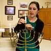 Samantha Schapera, student rabbi, lights a Menorah before the first night of Hanukkah at the United Hebrew Congregation Temple on Sunday.<br /> Globe | Roger Nomer