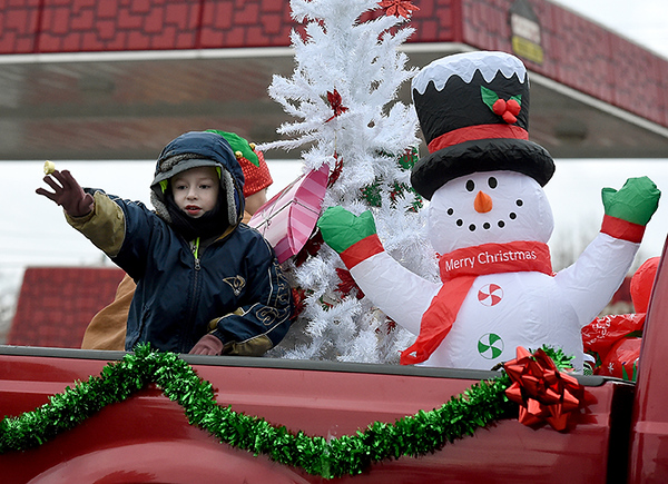 A child waves from the bed of a truck with a wintry scene during the Galena Christmas Parade on Saturday in downtown Galena.<br /> Globe | Laurie Sisk