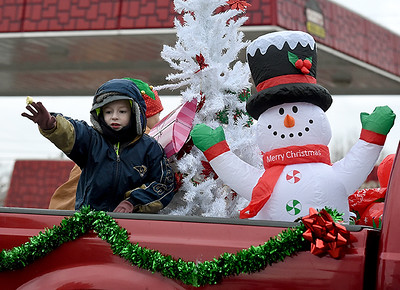 A child waves from the bed of a truck with a wintry scene during the Galena Christmas Parade on Saturday in downtown Galena. Globe | Laurie Sisk