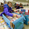 From the left: On Saturday at the Newton County Fairgrounds, St. Marys students Samantha Lone, 7 and her sister Bethany Lone, 11, organize some of the more than 2,000 boxes of Jello their school collected for the Newton County Food Basket Brigade. This year's efforts involved about 1,000 volunteers and will feed 525 Newton County families this holiday.<br /> Globe | Laurie Sisk