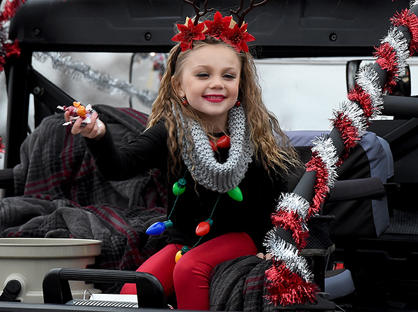 Five-year-old Taytum Scott tosses candy to other children from the back of a Jeep during the Galena Christmas Parade on Saturday in downtown Galena.<br /> Globe | Laurie Sisk