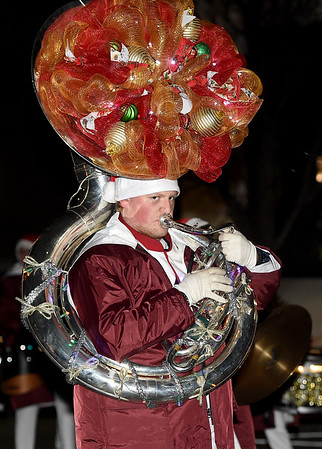 A member of The Eagle Pride Marching Band playsba festively decorated sousaphone as the Joplin band helps kick off the 2018 Christmas Parade on Tuesday night in Downtown Joplin.<br /> Globe | Laurie Sisk
