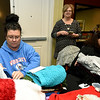 Ann Leach, center, shares her strategy for distribution of more than 1,000 hats, scarves and gloves as part of the Chase the Chill program on Thursday night at Homewood Suites as volunteers Brandy Duley, left and Kathy Mason, right, tag items with message of love. Duley and Mason are two of the seven Freeman Health Systems volunteers who helped collect, organize and tag the items.<br /> Globe | Laurie SIsk