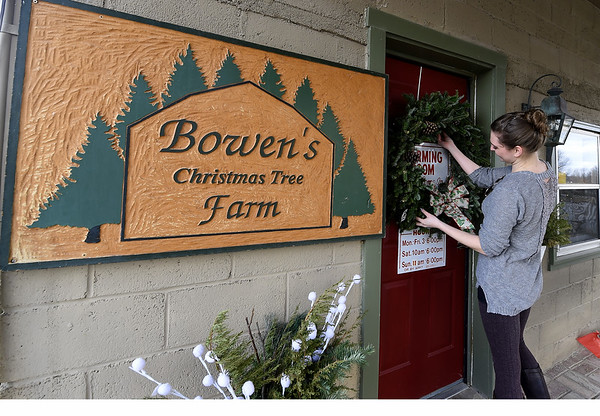 Jim and Karen Bowen's granddaughter, Victoria Bowen Bunch, hangs a wreath on the door of the Warming Room on Thursday. Like many in the Bowen family, Victoria has helped at the business, specifically creating wreaths for sale at the gift shop.<br /> Globe | Laurie Sisk