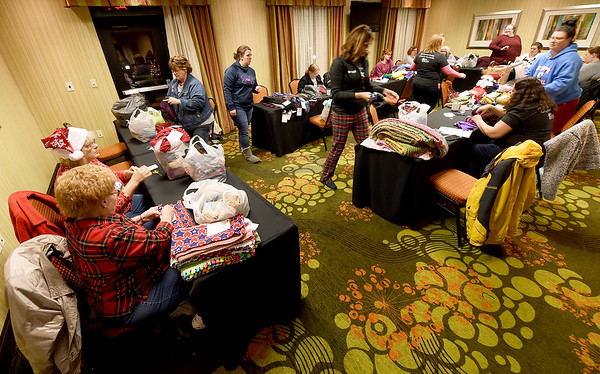 A small army of volunteers tag new scarves, hats and gloves for distribution throughout the Joplin community as part of the Chase the Chill program on Thursday night at Homewood Suites. Volunteers will distribute more than 1,000 items as part of the program, which is in its fourth year.<br /> Globe | Laurie Sisk