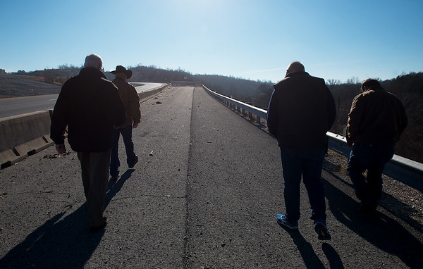 (from left) Rep. Bill Lant, presiding McDonald County commissioner elect, John Bunch, eastern McDonald County commissioner, Gregg Sweeten, Pineville mayor, and David Holloway, associate McDonald County commissioner, walk towards the end of the incomplete bypass on the Missouri side on Monday.<br /> Globe | Roger Nomer