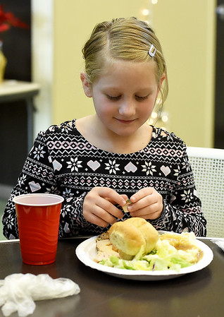 After volunteering, Aspen Ritchie, 8, enjoys a little Christmas dinner during the Carl Junction Community Christmas Dinner on Tuesday at the Carl Junction Community Center.<br /> Globe   Laurie Sisk