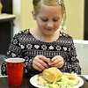 After volunteering, Aspen Ritchie, 8, enjoys a little Christmas dinner during the Carl Junction Community Christmas Dinner on Tuesday at the Carl Junction Community Center.<br /> Globe | Laurie Sisk