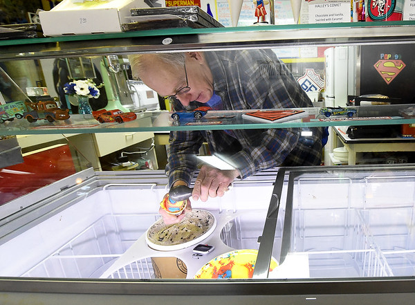 SuperTam on 66 owner Larry Tamminen scoops some of his popular Superman ice cream inside his ice cream store and Superman museum on Tuesday afternoon. The store is a popular stop for tourists traveling on historic Route 66.<br /> Globe | Laurie Sisk