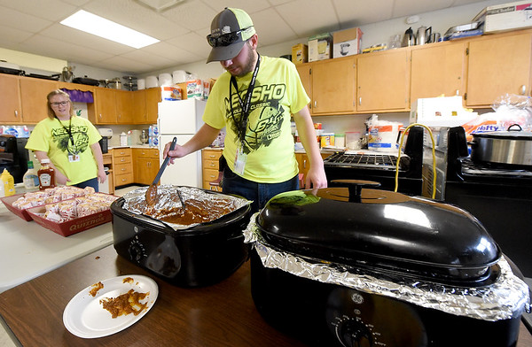 Branco volunteer Dustin Branham stirs chili for nachos as Lakin Larimore looks on in one of four hospitality rooms during the 2018 Neosho Holiday Classic on Thursday afternoon at NHS. More than 40 volunteers help feed players, coaches, media and officials after each game in the tournament.<br /> Globe   Laurie Sisk